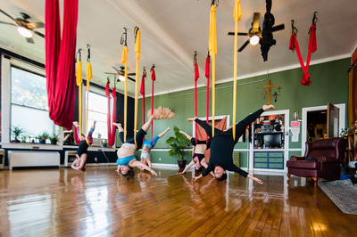 a group of 5 plus size women upside down hanging from silks in an aerial yoga class