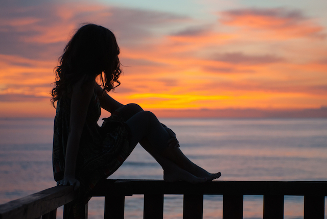 young woman sitting on a balcony by the sea and waiting the sunrise