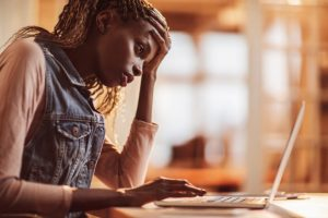 A person sits in front of a laptop, appearing worried, with one hand touching their forehead.