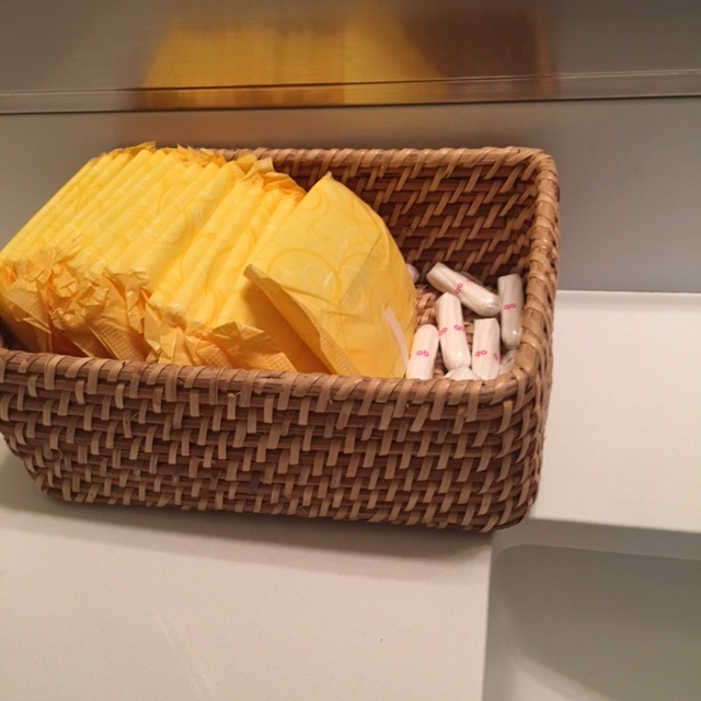 a wicker basket with menstrual supplies