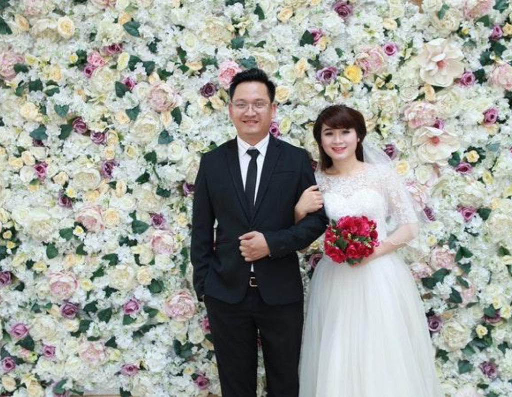 An Asian bride and groom smile in front of a wall of flowers.