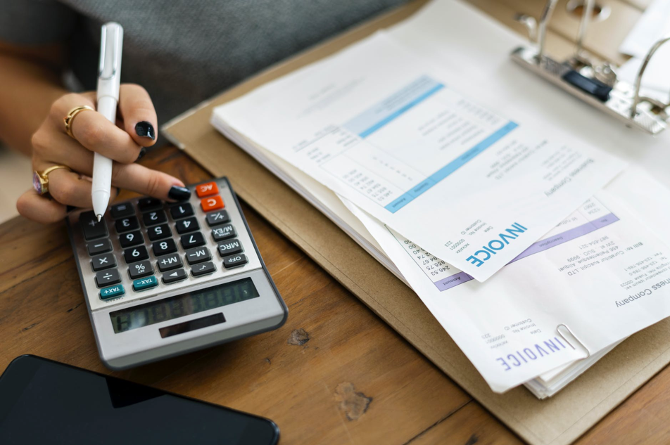 Image of woman's hands calculating bills.